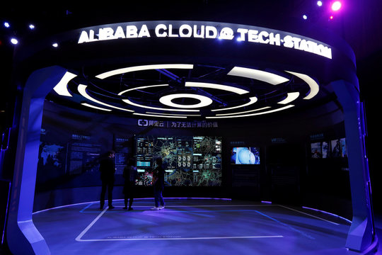 Visitors stand inside a booth introducing Alibaba Cloud services at an exhibition venue during Alibaba Group's 11.11 Singles' Day global shopping festival in Shenzhen