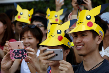 People wearing 'Pikachu' hats take pictures of the parade by performers wearing Pokemon's character Pikachu costumes in Yokohama