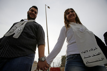 Activists stand hand-in-hand to protest against family violence during a rally in Beirut