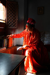 Living Goddess Kumari Chanira Bajracharya looks for a book while studying at her residence at Patan in Nepal