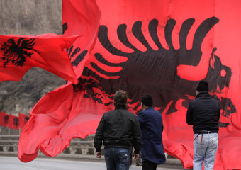 Kosovo Albanians stand near Albanian national flags set up in the town of Kacanik