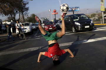 Colombian soccer fan Fernando Montoya controls the ball during a freestyle football show before the Copa America semi-final soccer match between Chile and Peru at the National Stadium in Santiago, Chile