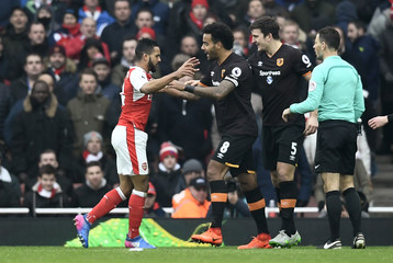 Arsenal's Theo Walcott clashes with Hull City's Harry Maguire and Tom Huddlestone as referee Mark Clattenburg looks on