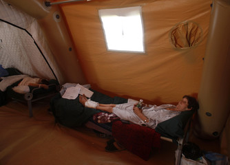 Earthquake victims lie in beds in a field hospital set up after a major earthquake destroyed a large swath of the coastline of southern Chile, in Talca
