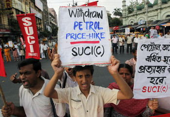 Activists from the Socialist Unity Centre of India (SUCI) hold placards while shouting slogans during a protest against a recent hike in petrol prices in Kolkata