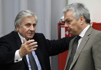 ECB President Trichet talks to Belgium's Finance Minister Reynders during an EU finance ministers meeting in Luxembourg
