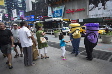 """People who dress up as """"Minions"""" from the """"Despicable Me"""" movies pose for photos and demand tips in Times Square, New York"""