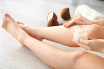 Woman applying coconut oil onto skin, closeup