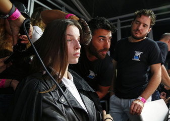 Hairstylists work backstage before the presentation of the Jean-Pierre Braganza Spring/Summer 2014 collection during London Fashion Week