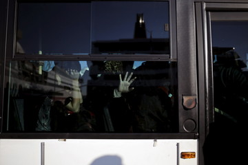 A migrant places her hand on a bus window at the port of Piraeus
