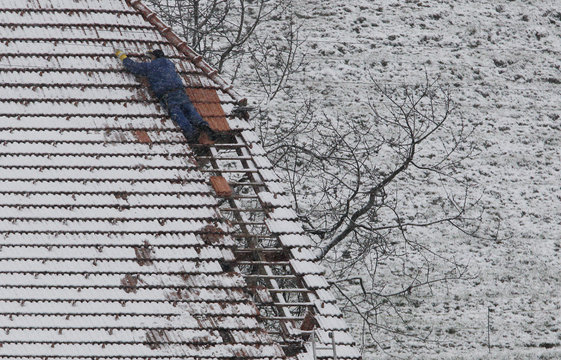 A roofer fixes a roof of a farmer's house after winter storm Joachim blowed away roofing tiles in Boll near Bern