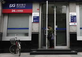 A woman leaves a branch of Shanghai Pudong Development Bank in Beijing