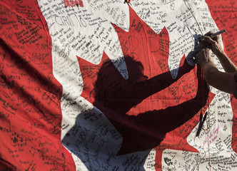 A woman writes a message on a Canadian flag at a makeshift memorial in honour of Cpl. Nathan Cirillo, outside the Lieutenant-Colonel John Weir Foote Armoury