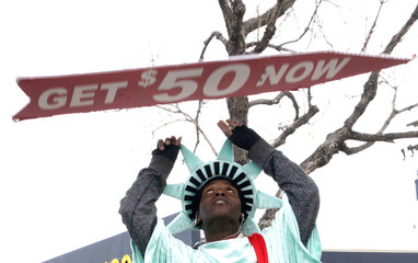 Manuel Martinez, dressed like the Statue of Liberty, flips a sign advertising the Liberty Tax preparation business in Denver
