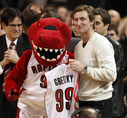 Hockey legend Gretzky receives a jersey from the Toronto Raptors mascot during their NBA basketball game in Toronto