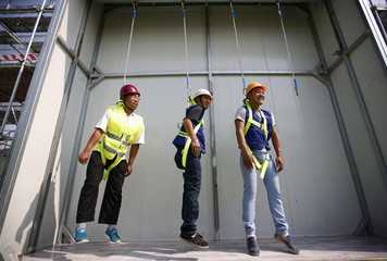 Participants hang from ropes as they learn how to use safety gears at an experience centre for construction safety training in Beijing