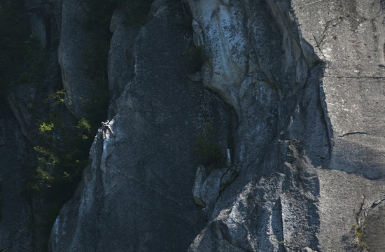 A rock climber scales the face of a mountain called The Chief in Squamish, British Columbia