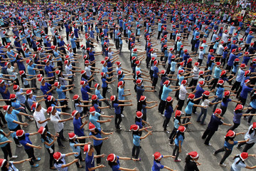 """Students wearing Santa Claus hats gesture as they perform to the tune of """"Jingle Bells"""" during a Christmas programme at a school oval in Manila"""