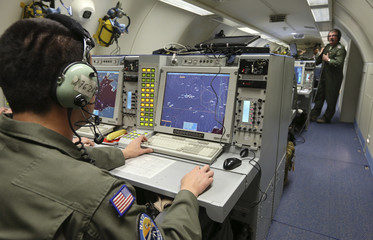A controller monitors screens aboard a NATO AWACS aircraft during surveillance flight over Romania