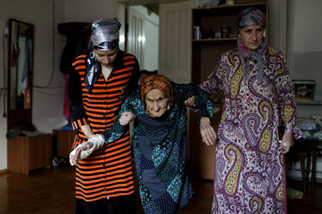 Relatives help Karuyeva, whose official documents showed she is the oldest person in the world, inside their house in the village of Goity