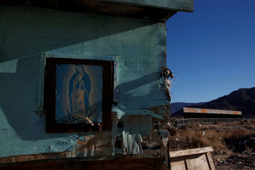 A framed picture of Our Lady of Guadalupe is seen at a house as a newly built section of the U.S.-Mexico border fence is seen in the background at Anapra neighbourhood in Ciudad Juarez