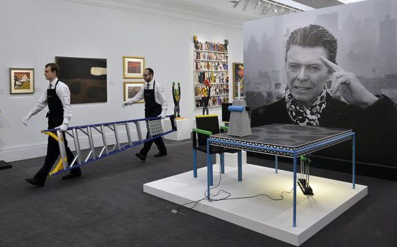 Technicians carry a ladder as they prepare for the exhibition of British pop star David Bowie's art collection at Sotheby's auction house, in central London