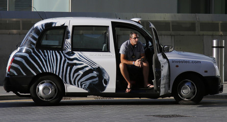 A taxi driver sits in his cab, adorned with a photo of a zebra, waits for customers outside the Docklands Light Railway station at Westfield shopping centre in Stratford