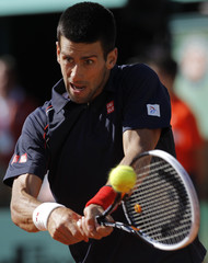 Djokovic of Serbia returns the ball to Federer of Switzerland during their men's singles semi-final match at the French Open tennis tournament at the Roland Garros stadium in Paris