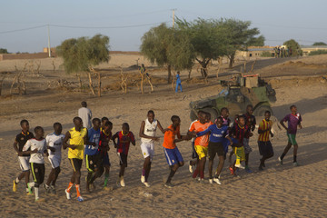 Soccer players run in front of a French armoured vehicle from Operation Barkhane on patrol in Timbuktu