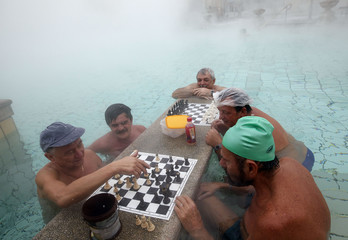 Bathers play chess while relaxing in Szechenyi Bath during a winter morning in Budapest