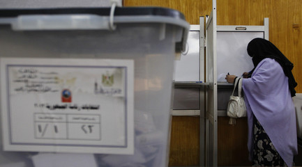 A woman marks her ballot before casting it at a polling station in Cairo