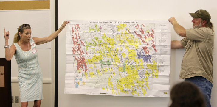"Skinner and Kemble hold a February/2013 map of the overall gas activity in Bradford County, Pennsylvania at the ""Stop the Frack Attack People's Forum"" in Washington"