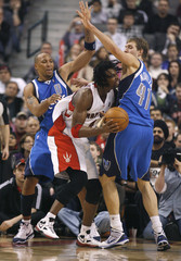 Raptors forward Bosh drives to the basket against Mavericks defenders Marion and Nowitzki during their NBA basketball game in Toronto