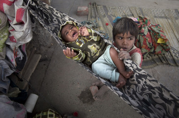 Boy rocks his sibling inside his family tent at a slum in the outskirts of Lahore Pakistan