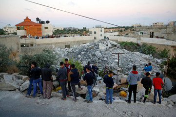 Palestinians gather around the family house of Palestinian assailant Murad Idais after it was demolished by Israeli forces in the West Bank village of Yatta,