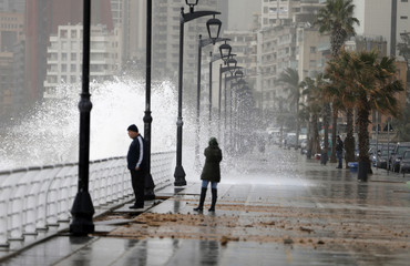 Residents stand by a crashing wave on Beirut's Corniche, a seaside promenade, as high winds sweep through Lebanon during a storm