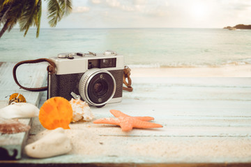 Fotomurales - The concept of leisure travel in the summer on a tropical beach seaside. retro camera on the sandbar with starfish, shells, coral on sandbar and blur sea background.  vintage color tone styles.