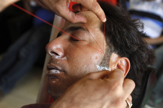 Alaa Hamed, 35-year-old Palestinian groom, gets a hair removal treatment before taking part in a mass wedding party for 19 Palestinian couples in the West Bank village of Silwad