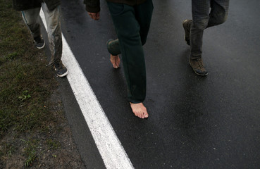Migrants walk along a road after crossing the border with Serbia in Babska