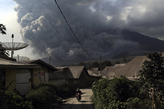 A villager leaves on a motorcycle as Mount Sinabung volcano spews ash in the background, at Berastepu village in Karo district