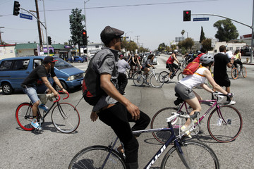 Bicycles riders stop traffic at the intersection of Florence and Normandie, where trucker Reginald Denny was beaten by four black men, setting off the 1992 LA riots, in Los Angeles
