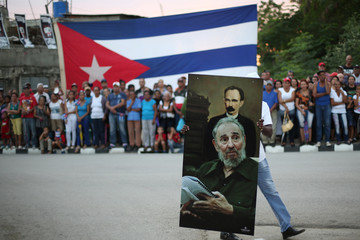 A man carries a picture showing Cuba's former President Fidel Castro and Jose Marti, as people line the street while waiting for the ashes of Castro to pass during a journey to the eastern city of Santiago de Cuba, in Bayamo