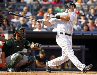 New York Yankees' Ibanez watches his solo home run with Oakland Athletics catcher Kottaras during fifth inning of their MLB American League baseball game in New York