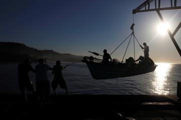 Men help fishermen as they arrive at the fishermen dock in La Libertad, El Salvador