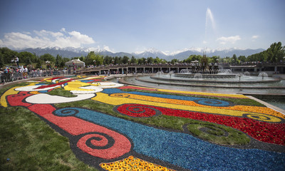 People visit a flower festival as Tien Shan mountains are seen on a background in Almaty