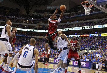 Miami Heat's Chris Bosh goes to the basket past Dallas Mavericks' Dirk Nowitzki (2nd-R) during Game 3 of the NBA Finals basketball series in Dallas