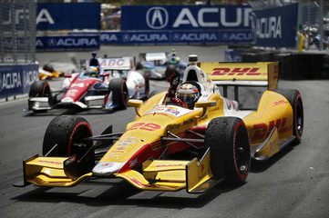 Hunter-Reay waves to the crowd on his victory lap after finishing first place at the Honda Indy car race in Toronto