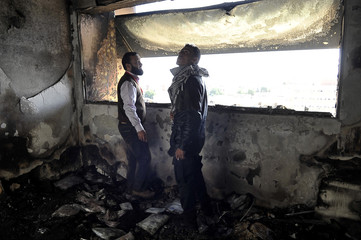 Hospital staff inspect the damage at the Benghazi Medical Center after a shell hit the sixth floor causing a fire in part of the building, according to the security office at the hospital, in Benghazi