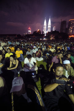"""People listen to Malaysia's opposition leader Anwar Ibrahim during the """"Free Anwar"""" rally against the background of landmark Petronas Twin Towers in Kuala Lumpur"""