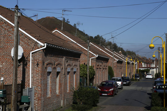 """A view shows a street with traditional northern France brick houses in the neighbourhood of closed metallurgical plant """"Usinor"""" with a slag heap in the background, in Denain"""